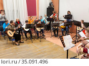 Classical music concert for parents is in Russian children academy of music. Young boys and girls with adults play quitar together (2020 год). Редакционное фото, фотограф Кекяляйнен Андрей / Фотобанк Лори