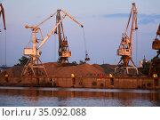 Level-luffing bulk-handling cranes load sand onto a barge in a river port in the evening light. Стоковое фото, фотограф Евгений Харитонов / Фотобанк Лори