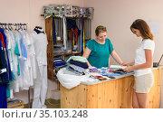 Портной показывает клиенту разнообразные варианты одежды под заказ в журнале. Стоковое фото, фотограф Иванов Алексей / Фотобанк Лори