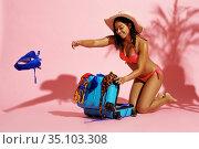 Happy woman in swimsuit unpacks suitcase in studio. Стоковое фото, фотограф Tryapitsyn Sergiy / Фотобанк Лори
