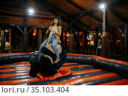 Woman on rodeo attraction in night amusement park. Стоковое фото, фотограф Tryapitsyn Sergiy / Фотобанк Лори