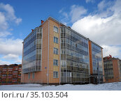 New residential brick apartment building with glazed balconies stands among the snow in the village of Tayozhny, Krasnoyarsk Territory. Russia. (2020 год). Стоковое фото, фотограф Светлана Попова / Фотобанк Лори