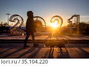 Женщина выгуливает собаку на фоне новогодней инсталляции в виде цифр нового года 2021 установленной в Парке Горького города Москвы, Россия. Редакционное фото, фотограф Николай Винокуров / Фотобанк Лори