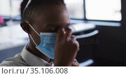 African american woman adjusting her face mask while sitting on her desk at modern office. Стоковое видео, агентство Wavebreak Media / Фотобанк Лори