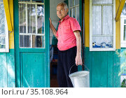 senior pensioner in red polo posing near the house in the village. Стоковое фото, фотограф Татьяна Яцевич / Фотобанк Лори