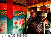 Tibetan Buddhist pilgrim praying at Ganden Thubchen Choekhorling Monastery. Litang, Garze Tibetan Autonomous Prefecture, Sichuan, China. 2016. Стоковое фото, фотограф Enrique Lopez-Tapia / Nature Picture Library / Фотобанк Лори