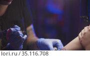 Tattoo session - getting a black abstract tattoo on her arm by a woman master. Стоковое видео, видеограф Константин Шишкин / Фотобанк Лори