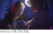 Tattoo session - getting a black abstract tattoo on her arm by a woman master in dark studio. Стоковое видео, видеограф Константин Шишкин / Фотобанк Лори