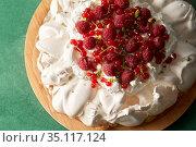 pavlova meringue cake with berries on wooden board. Стоковое фото, фотограф Syda Productions / Фотобанк Лори