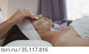 Caucasian woman lying back while beautician gives her a facial. Стоковое видео, агентство Wavebreak Media / Фотобанк Лори