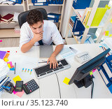 Businessman working in the office with piles of books and papers. Стоковое фото, фотограф Elnur / Фотобанк Лори