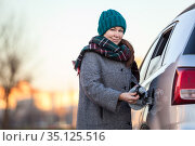 Positive Caucasian female driver portrait with opened gas cap lid of her car, looking at camera. Стоковое фото, фотограф Кекяляйнен Андрей / Фотобанк Лори