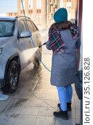 Attractive Caucasian woman with high pressure hose washing her suv in self service station at cold season. Стоковое фото, фотограф Кекяляйнен Андрей / Фотобанк Лори