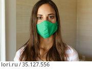 Portrait of caucasian woman wearing green face mask looking straight to camera. Стоковое фото, агентство Wavebreak Media / Фотобанк Лори