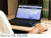 Russia Samara July 2020: A young man during the coronavirus epidemic watches facebook on a laptop at night. Редакционное фото, фотограф Акиньшин Владимир / Фотобанк Лори