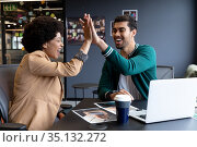 Happy diverse businessman and businesswoman high fiving in creative office. Стоковое фото, агентство Wavebreak Media / Фотобанк Лори