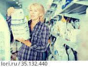 mature woman purchasing pet food in petshop. Стоковое фото, фотограф Татьяна Яцевич / Фотобанк Лори
