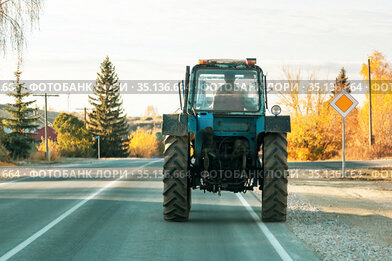 Old rusty vintage tractor of blue color is driving along the road in a village in Russia in summer, rural life in the Saratov region