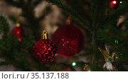 Гирлянда на елке освещает красные блестящие шары. Новогоднее украшение. Стоковое видео, видеограф Мiлана Х / Фотобанк Лори