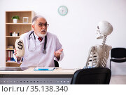 Old male doctor cardiologist and skeleton patient in expensive m. Стоковое фото, фотограф Elnur / Фотобанк Лори