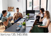 team of startuppers drinking coffee at office. Стоковое фото, фотограф Syda Productions / Фотобанк Лори