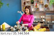 Pleasant Vietnamese woman in a red dress prepares traditional Vietnamese tea. Стоковое фото, фотограф Алексей Кузнецов / Фотобанк Лори