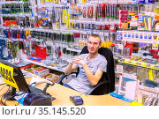 Russia Samara July 2020: a handsome young seller of locksmith tools at his workplace at a table from a computer. Russian text: checkout. Редакционное фото, фотограф Акиньшин Владимир / Фотобанк Лори