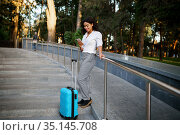 Smiling woman with suitcase on the stairs in park. Стоковое фото, фотограф Tryapitsyn Sergiy / Фотобанк Лори