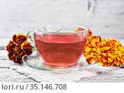 Чай травяной из бархатцев в чашке на старой доске. Стоковое фото, фотограф Резеда Костылева / Фотобанк Лори