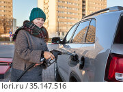 Attractive woman inserting fuel pump nozzle for filling diesel in her car at self-service urban petrol station. Стоковое фото, фотограф Кекяляйнен Андрей / Фотобанк Лори