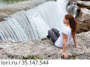 Attractive woman with curly hairs sitting on rock and enjoying of the cascade of Cijevna river. It is called Montenegrin Niagara Falls. Surroundings of Podgorica city. Montenegro, Balkans, Europe. Стоковое фото, фотограф Кекяляйнен Андрей / Фотобанк Лори