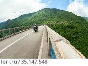 Motorcyclists drive on asphalt road of Durdevica Bridge. The Durdevica Bridge is a famous attraction in Durmitor national park. It is across Tara river. Montenegro (2016 год). Редакционное фото, фотограф Кекяляйнен Андрей / Фотобанк Лори