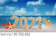 Concept of celebrating the new year in hot countries. The inscription 2021 in the sand and a snowflake on a bright day on the beach. Стоковое фото, фотограф Сергей Молодиков / Фотобанк Лори