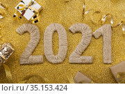 Lettering 2021 from handmade twine on gold with champagne bottle and ribbon. Стоковое фото, фотограф Сергей Молодиков / Фотобанк Лори