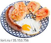 Fried eggs with sausage and baguette slices. Стоковое фото, фотограф Яков Филимонов / Фотобанк Лори