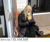 Пассажиры в московском метро в медицинской маске. Стоковое фото, фотограф Victoria Demidova / Фотобанк Лори