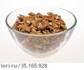 Очищенные ядра грецких орехов в прозрачной глубокой тарелке на светлом фоне. Стоковое фото, фотограф Румянцева Наталия / Фотобанк Лори