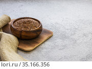 Flax seeds in a wooden bowl on a concrete background, dietary cereal ingredient, cholesterol lowering product, a source of omega-3, vitamin B and C, iodine, phosphorus, potassium, magnesium, nickel. Стоковое фото, фотограф Светлана Евграфова / Фотобанк Лори