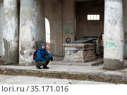 VOLZHSKY, RUSSIA - NOVEMBER 15, 2020: A man sits near a robbery in Mortuary or pantheon, on the territory of cemetery Nomer 1 in the city of Volzhsky. Редакционное фото, фотограф Владимир Арсентьев / Фотобанк Лори