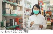 Portrait of chinese female druggist in protective facial mask working in pharmacy. Стоковое видео, видеограф Яков Филимонов / Фотобанк Лори