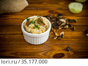 cooked rice with dried forest mushrooms on a wooden table. Стоковое фото, фотограф Peredniankina / Фотобанк Лори