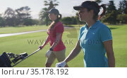 Two female caucasian golf players walking with their golf kit carts on the golf course. Стоковое видео, агентство Wavebreak Media / Фотобанк Лори