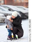 Young mom comforts the child after falling down on slippery road, hugging a toddler. Стоковое фото, фотограф Кекяляйнен Андрей / Фотобанк Лори