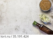Linseed oil in a bottle, flax seeds, salad dressing in a gravy boat source of omega-3 and fatty acids on a table on a natural gray concrete background top view. Стоковое фото, фотограф Светлана Евграфова / Фотобанк Лори