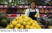 Supermarket employee in apron checking products in vegetable department. Стоковое видео, видеограф Яков Филимонов / Фотобанк Лори