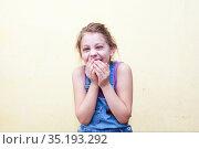 Happy eight years old adorable girl in denim jumpsuit on yellow studio background. Стоковое фото, фотограф Дарья Филимонова / Фотобанк Лори