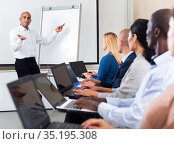 Hispanic business coach giving talk before participants with laptops. Стоковое фото, фотограф Яков Филимонов / Фотобанк Лори