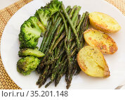 lean dish of cooked fried inflorescences of broccoli, asparagus growth and baked potatoes and Provencal herbs. Стоковое фото, фотограф Татьяна Яцевич / Фотобанк Лори