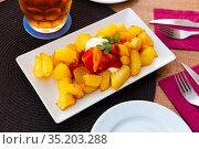 Close up of traditional spanish patatas bravas on plate on tablecloth. Стоковое фото, фотограф Яков Филимонов / Фотобанк Лори