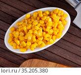 Plate with grains of boiled corn on wooden table. Стоковое фото, фотограф Яков Филимонов / Фотобанк Лори
